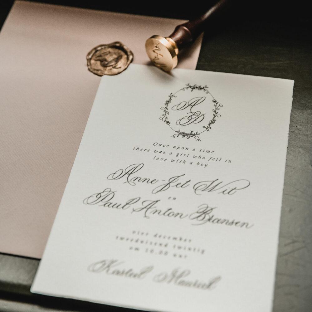 uitnodiging met klassieke kalligrafie en krans