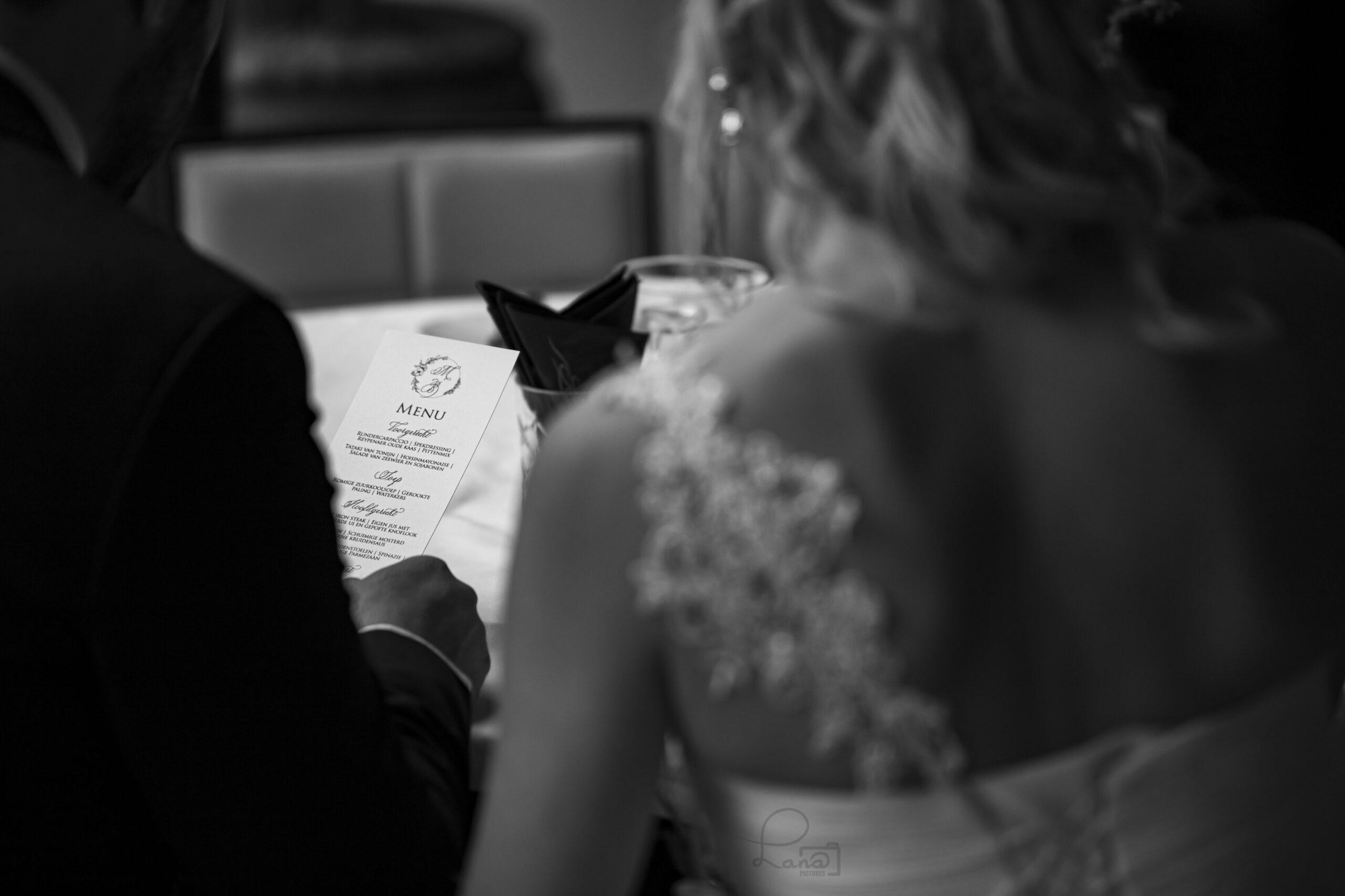 bruidspaar met menukaart in kalligrafie